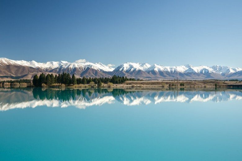 Turquoise Reflections, New Zealand Fine Art Photo Print. Lake Ruataniwha with its milky, turquoise water reflects the snow capped mountain ranges around Twizel. The clarity of this landscape invokes a sense of peacefulness.